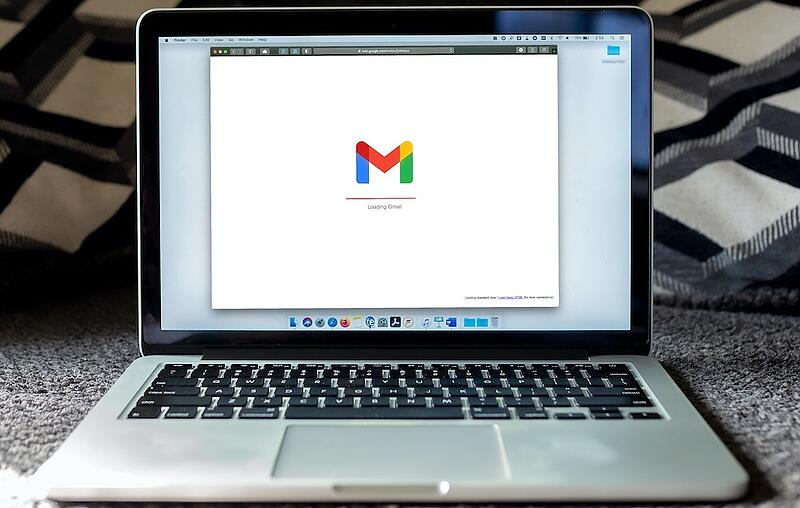 A mac laptop sits open with gmail loading on the screen