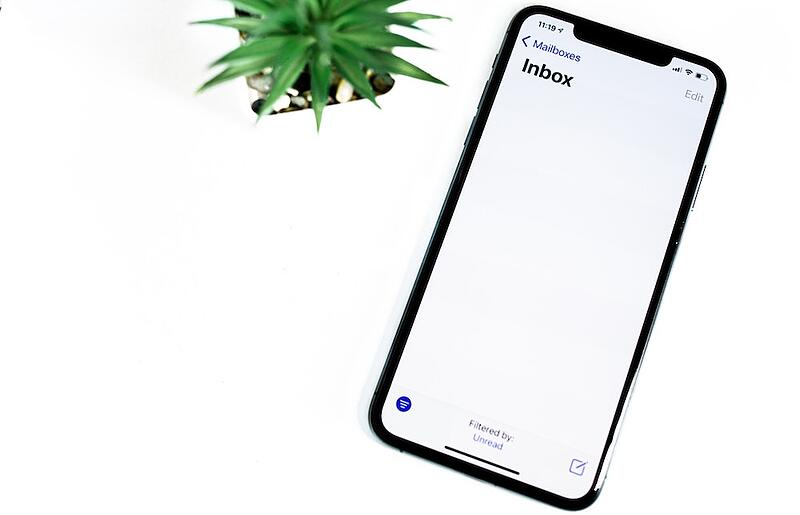 A phone with a mostly blank screen with just inbox in the top left corner