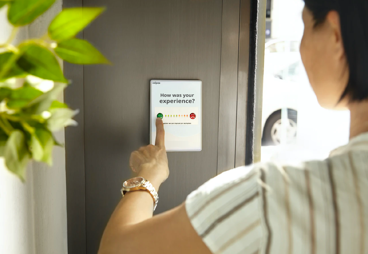 A women leaves feedback on a wall-mounted tablet which prompts 'how was your experience'.
