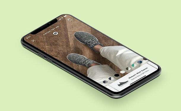 A cellphone shows a customer using AR to try on a pair of AllBirds