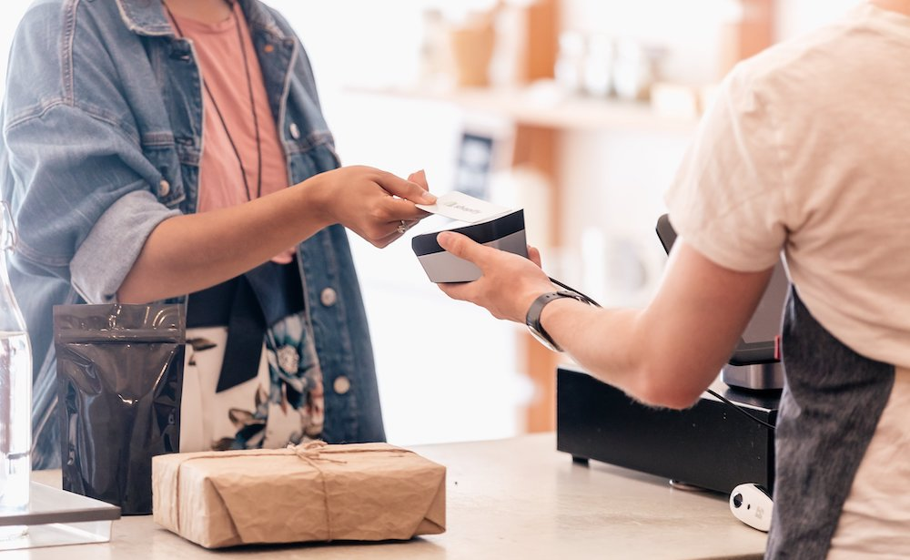 A customer hands a card to a shop cashier to pay for goods