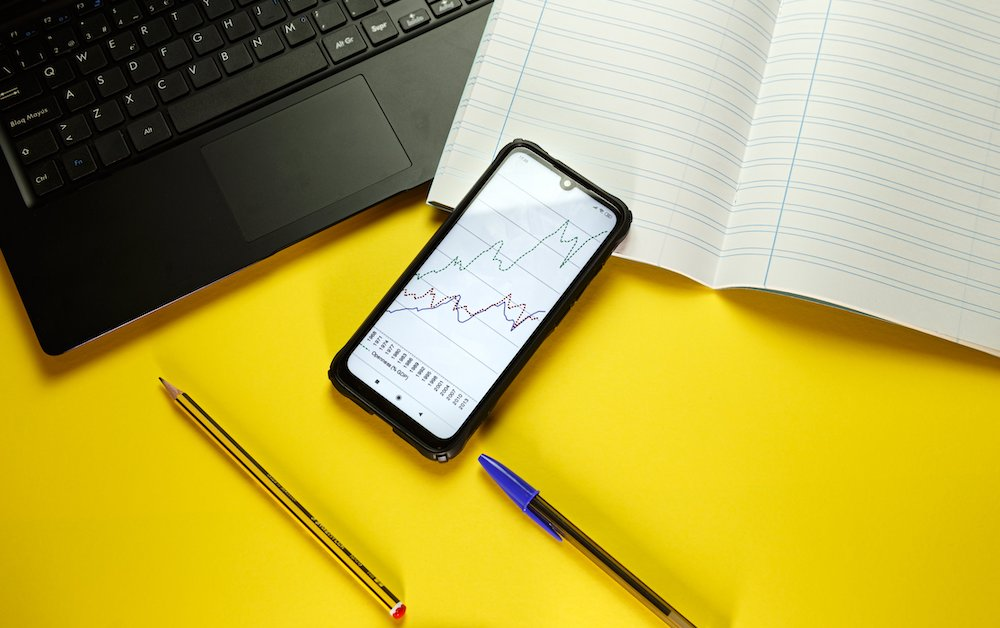 Flatlay of a laptop and open notebook with a cellphone showing graphs and a pen and pencil laying on a bright yellow background