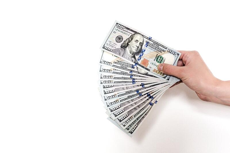 a hand holding multiple american hundred dollar bills.
