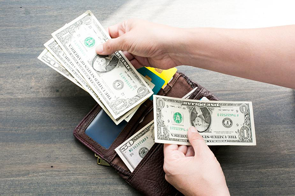 An open wallet with a person counting out $23