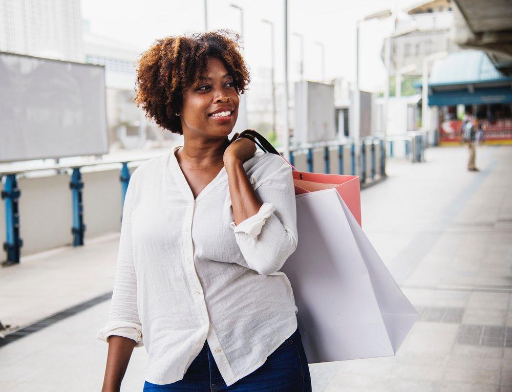 woman in a shopping center carrying shopping bags