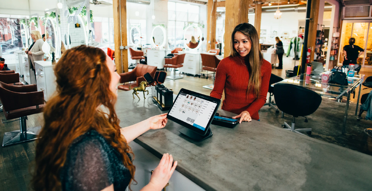 A retailer and a customer using an in-store POS system while smiling and chatting.
