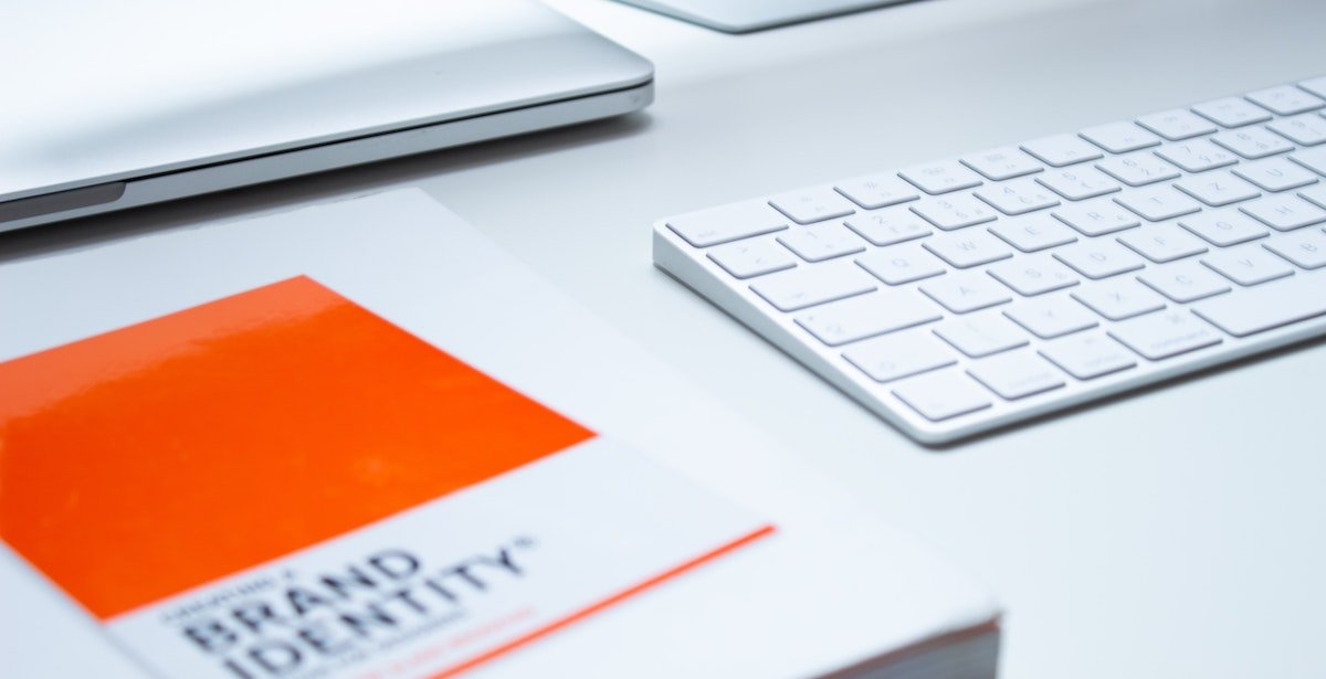 A book titled 'Brand Identity' sits on a desk next to a keyboard