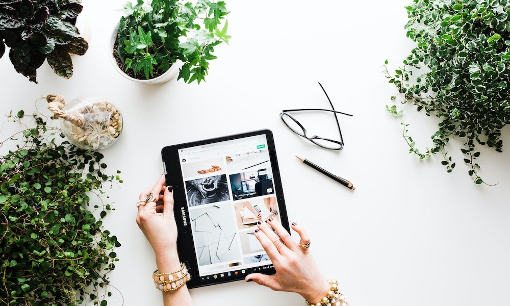 Birds-eye shot of feminine hands holding a tablet and scrolling through images. House plants sit on the table around the hands.