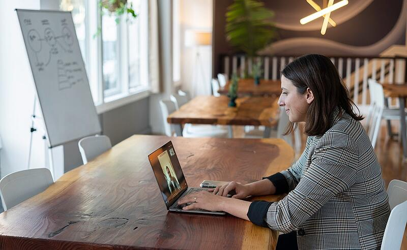 a woman uses a video conferencing software at an open-plan office space