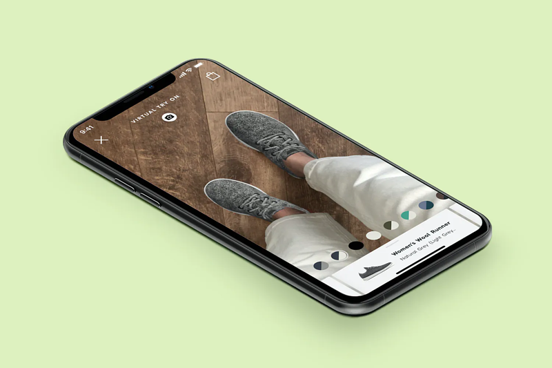 A phone rests on a green background with AllBird's AR technology in use on the screen.
